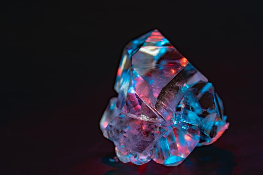 Diamant brut s'éclairant de couleurs multiples sous la lumière   Lithothérapie en Ligne